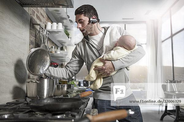 Vater mit Headset Kochen in der Küche hält Baby