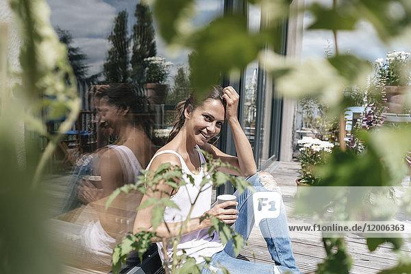 Lächelnde Frau entspannt auf dem Balkon