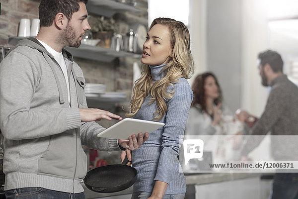 Paare diskutieren mit digitalem Tablettenrezept bei der Zubereitung einer Mahlzeit
