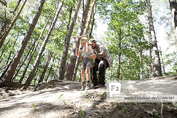 Vater mit Sohn auf Schaukel im Wald