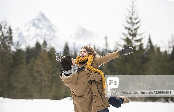 Glückliches junges Paar mit Spaß in der Winterlandschaft