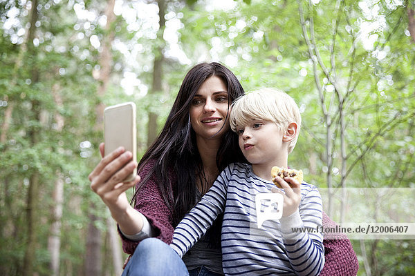 Mother and son taking a selfie in forest