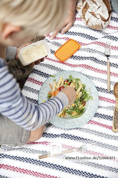 Junge verteilt geriebenen Käse auf Nudelsalat bei einem Picknick im Wald