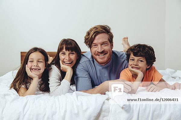 Porträt der Eltern und ihrer Kinder im Bett
