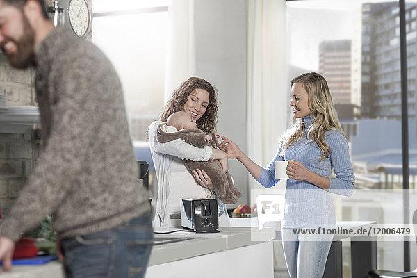 Mutter und Freundin mit Baby in der Küche