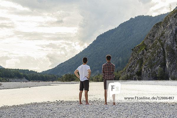 Deutschland  Bayern  Rückansicht von zwei Freunden mit Blick auf das Flussufer
