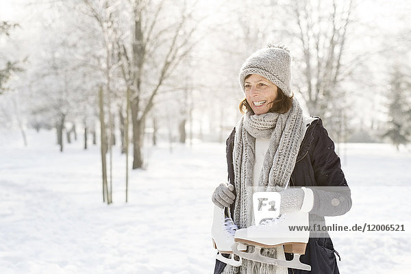 Smiling senior woman with ice skates in winter forest