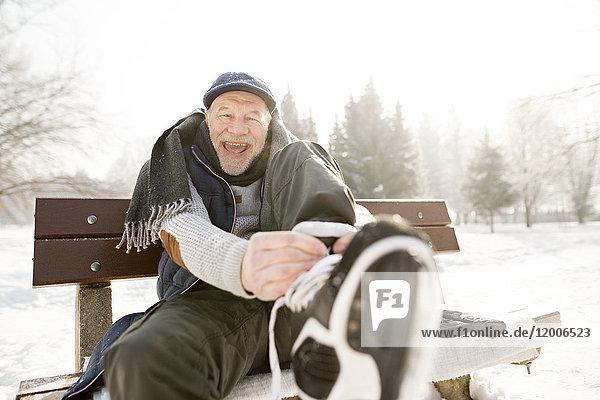 Porträt eines glücklichen älteren Mannes  der auf einer Bank in der Winterlandschaft sitzt und Schlittschuhe anzieht.