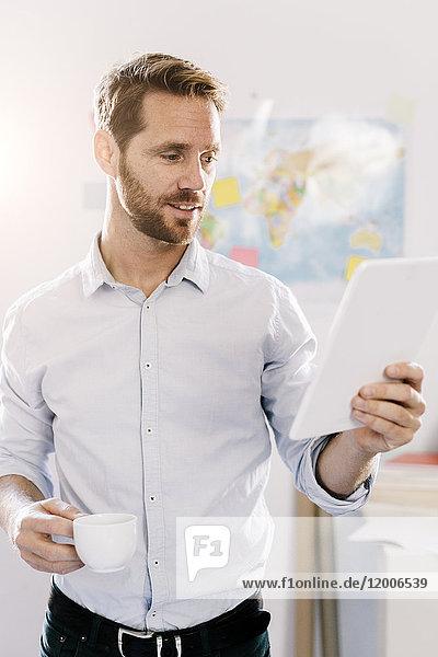 Bärtiger Mann im Büro mit einer Tasse Kaffee und Blick auf die Tablette