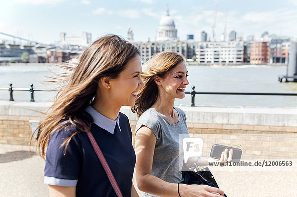 UK  London  two women walking along the banks of the Thames River