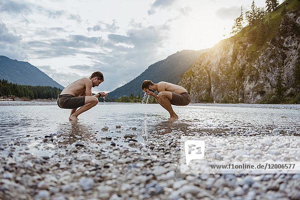 Deutschland  Bayern  zwei Freunde  die sich am Flussufer das Gesicht waschen