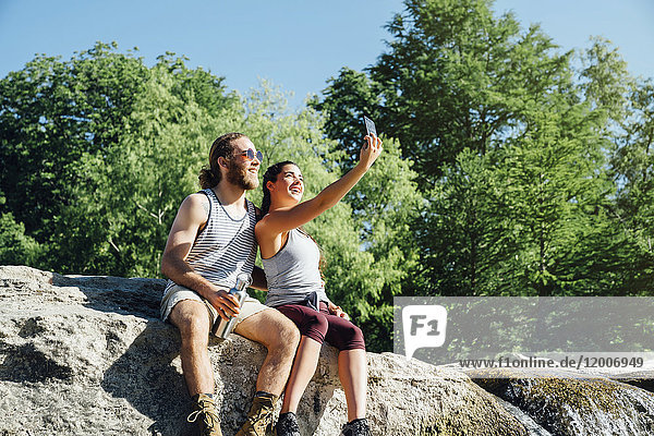 Caucasian couple posing for cell phone selfie on rocks