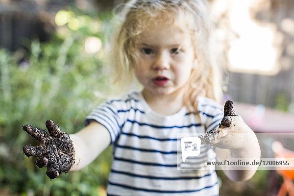 Caucasian girl with muddy hands in garden