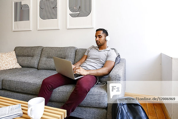 Mixed race man sitting on sofa listening to laptop with headphones