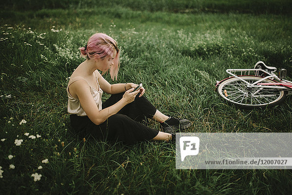 Caucasian woman sitting infield texting on cell phone