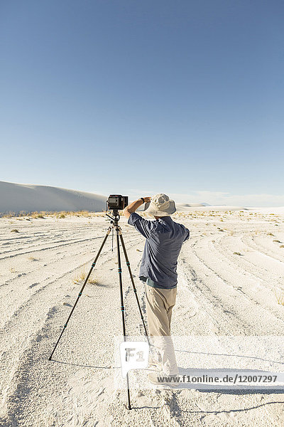 Caucasian photographer with tripod in desert
