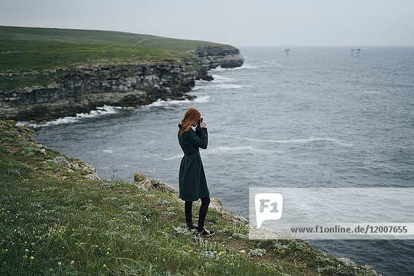 Caucasian woman photographing ocean