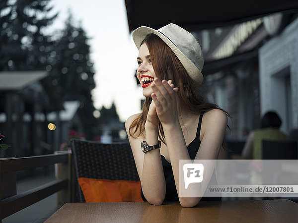 Caucasian woman at sidewalk cafe laughing