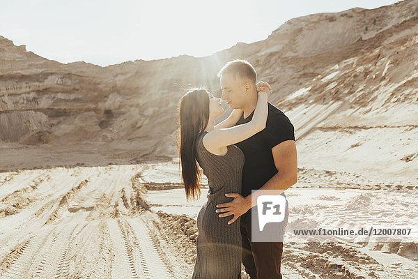 Middle Eastern couple kissing in desert