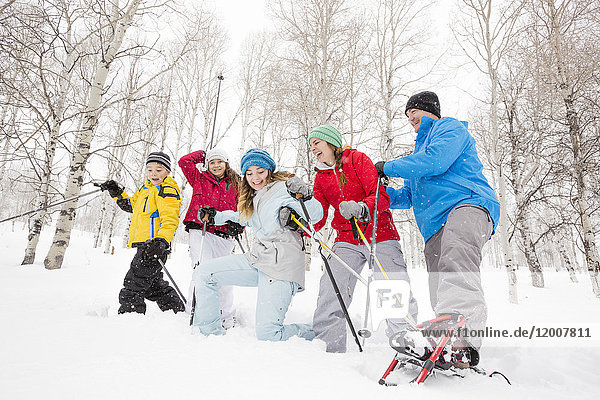 Smiling Caucasian family snowshoeing