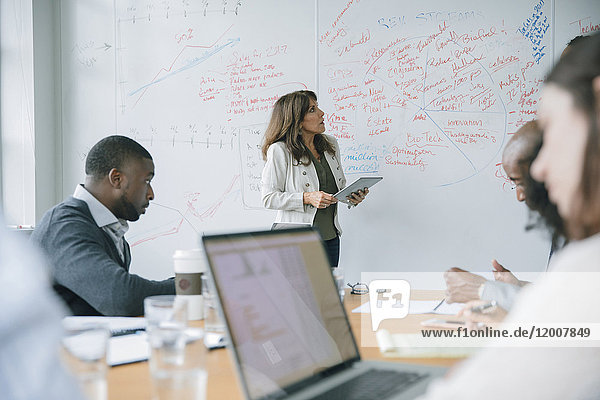 Businesswoman holding digital tablet near whiteboard in meeting