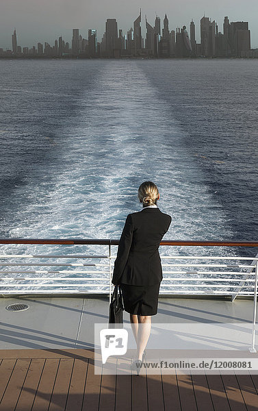 Caucasian businesswoman on boat leaving city