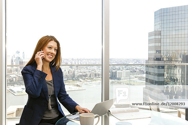 Caucasian businesswoman talking on cell phone and using laptop