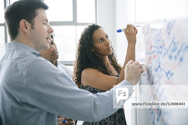 Business people writing on whiteboard in meeting