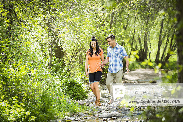 Couple walking in the woods holding hands
