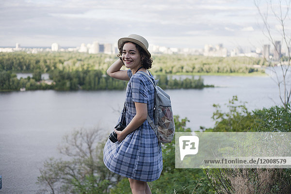 Portrait of a Caucasian woman carrying camera near river