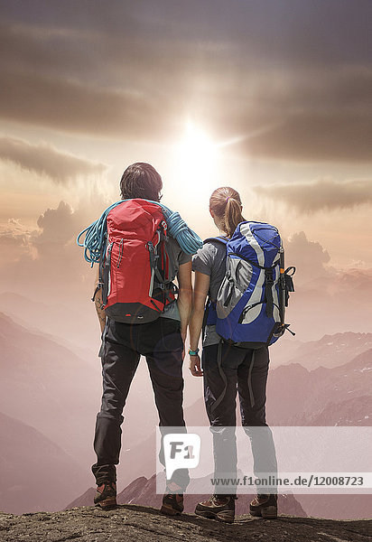 Caucasian hikers on mountain admiring sunset