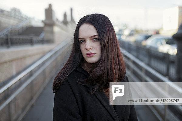 Serious Caucasian girl standing on footbridge