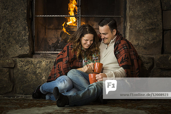 Smiling Caucasian couple cuddling on floor near fireplace