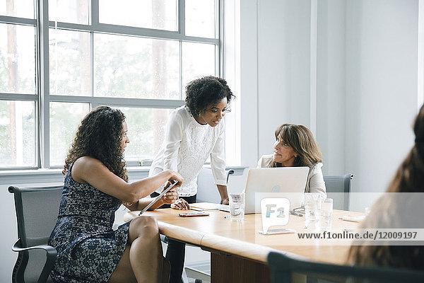 Businesswomen using laptop in meeting