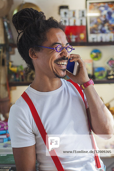 Laughing mixed race man wearing suspenders talking on cell phone