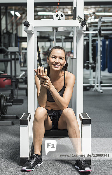 Mixed race woman rubbing wrist in gymnasium