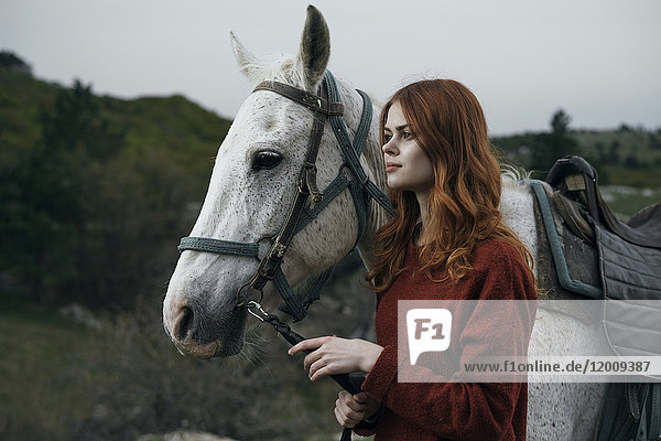 Caucasian woman holding rein of horse