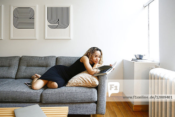 Mixed race woman laying on sofa reading book