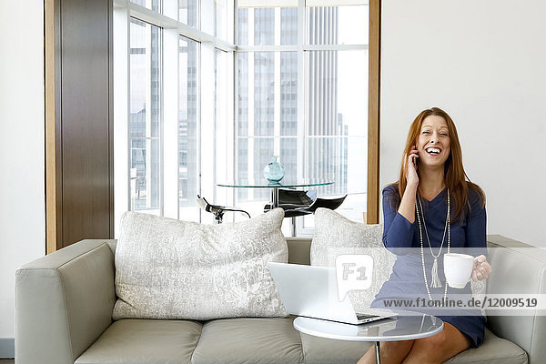 Caucasian businesswoman talking on cell phone and laughing