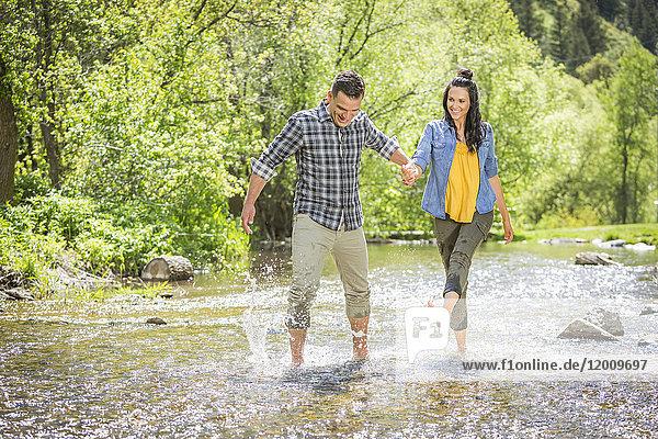 Woman kicking water on man in river