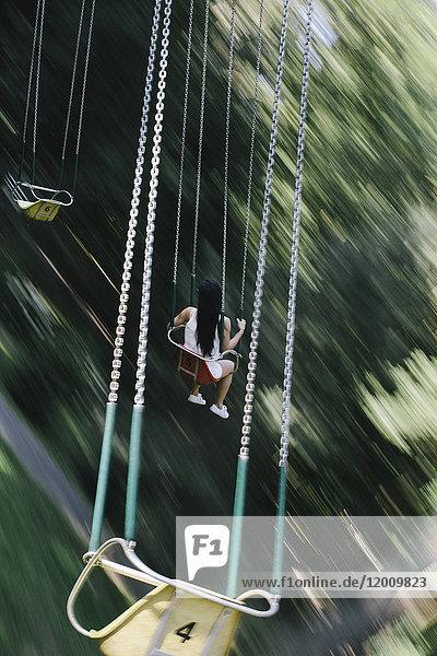 Woman riding amusement park swing