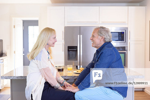 Caucasian couple holding hands in kitchen