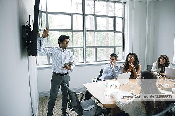 Businessman talking near visual screen in meeting