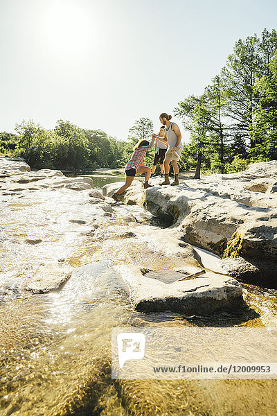 Man helping woman crossing river
