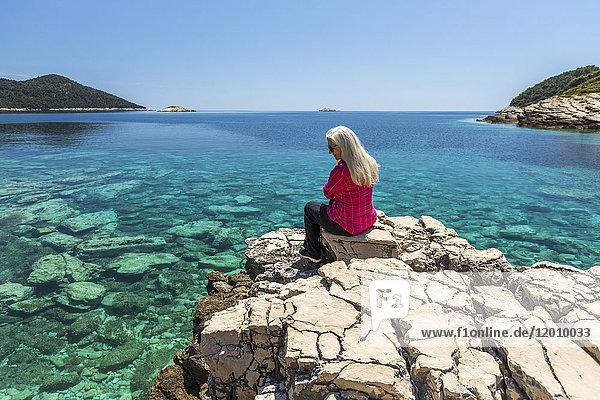 Caucasian woman sitting on rock admiring lake