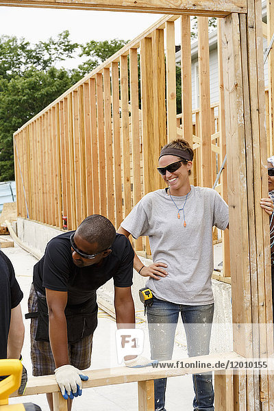 Volunteers holding frame at construction site