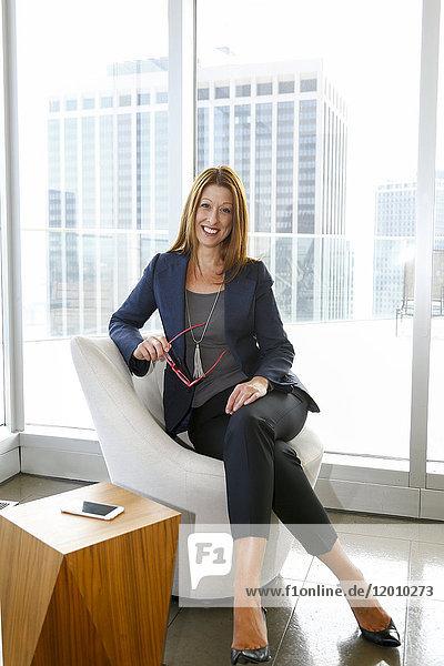 Portrait of Caucasian businesswoman sitting on chair holding eyeglasses