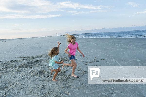 Caucasian sisters running on windy beach