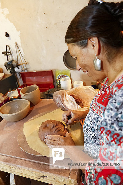 Mixed race woman shaping clay mask in art studio
