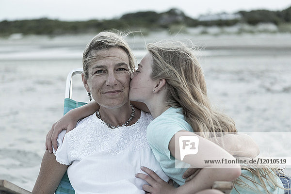 Caucasian girl kissing mother on cheek at windy beach